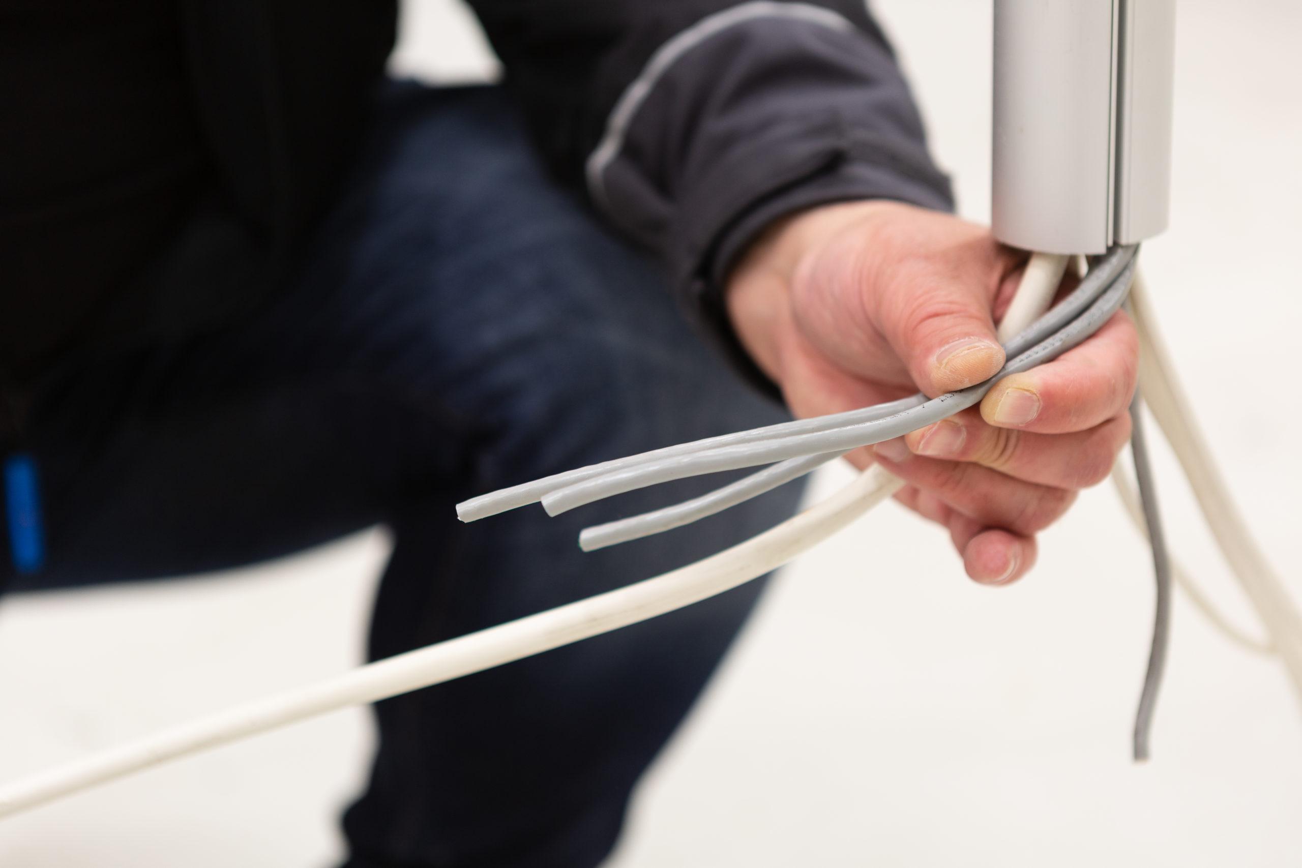 hånd holder et sett med ledninger på nært hold