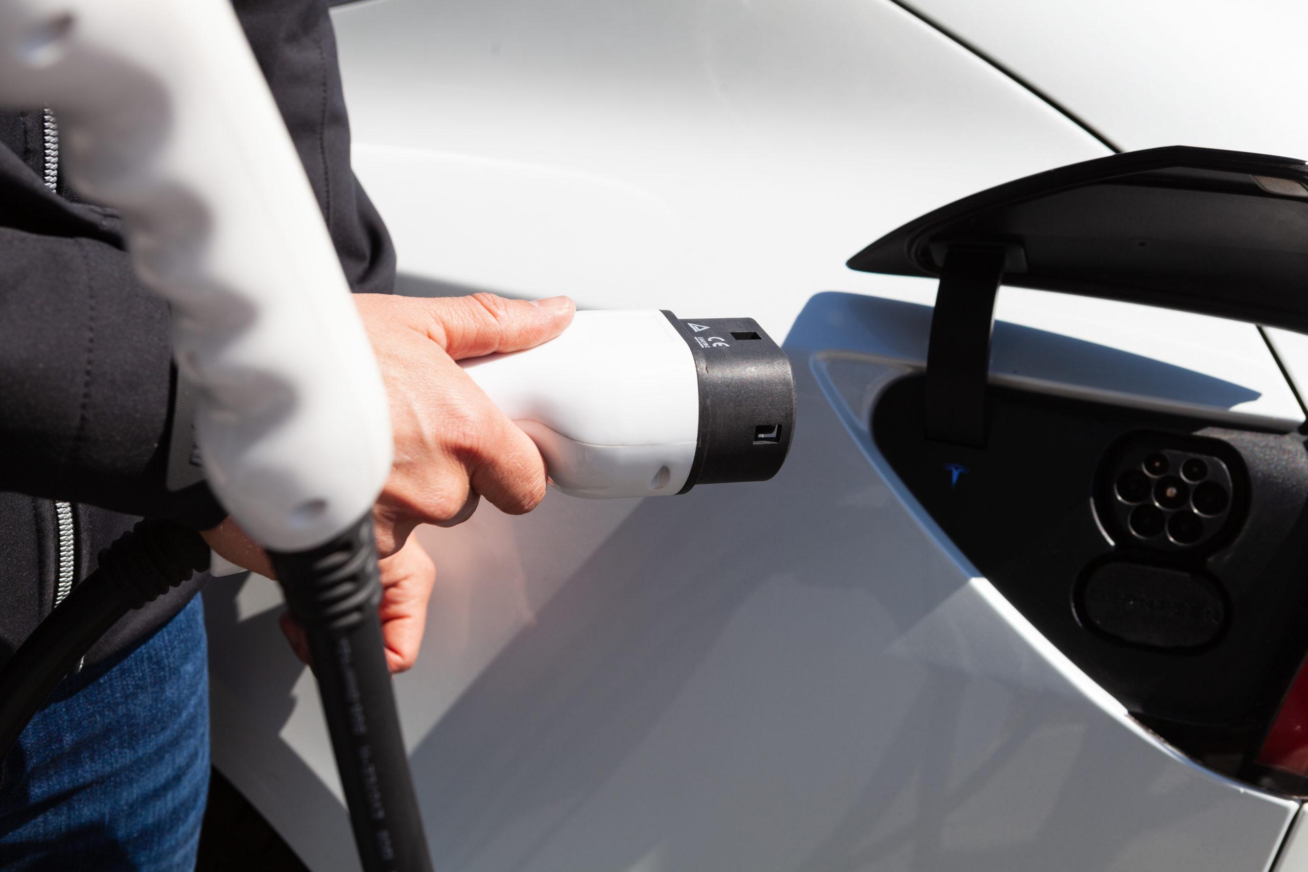 nærbilde av hånd som setter en lader inn i en elbil